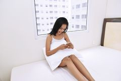 Happy asian woman with pillow using smartphone and relaxing. On the bed Stock Photos