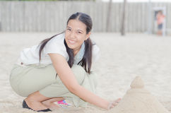 Happy Asian Woman play Castle Sand Stock Photo