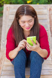 Happy asian woman is playing and chatting on her mobile phone Royalty Free Stock Photography