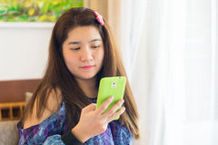 Happy asian woman is playing and texting on her mobile phone Stock Image