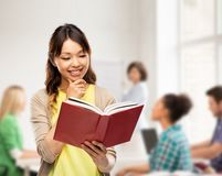 Happy asian woman reading book at school. Education, school and knowledge concept - happy asian young women reading book over classroom background royalty free stock photography