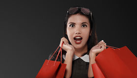 Happy asian woman with red shopping bag celebrating Black Friday. Over black background Royalty Free Stock Image