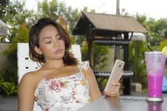 Happy Asian woman relaxed outdoors at coffee shop resort terrace with fruit juice using mobile phone texting and networking Stock Photo
