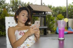 Happy Asian woman relaxed outdoors at coffee shop resort terrace with fruit juice using mobile phone texting and networking Stock Images