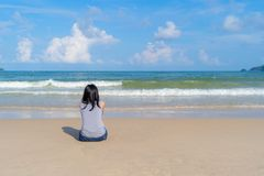 Happy Asian woman relaxing and enjoying at the beach during travel holidays vacation outdoors at ocean or nature sea at noon,. Phuket, Thailand royalty free stock photo