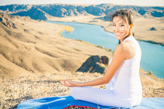 Happy asian woman relaxing and meditating above river valley Stock Photos