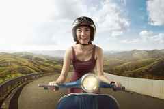 Happy asian woman riding blue scooter with helmet. Through mountain road Stock Image