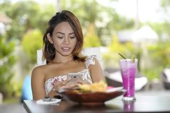 Happy Asian woman in dress at pool holiday resort having br stock photography