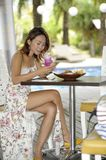Happy Asian woman in sexy dress at pool holiday resort having br. Young beautiful and happy Asian woman in sexy dress sitting at pool holiday resort having Royalty Free Stock Photo