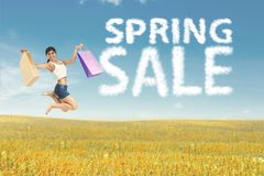Happy Asian woman with shopping bags jumping on meadow. Summer or spring concept Royalty Free Stock Image