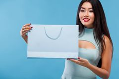 Happy asian woman at shopping holding bag and phone isolated on blue background on black friday holiday. Copy space for Stock Photos