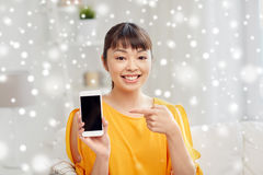 Happy asian woman showing smartphone at home Stock Image