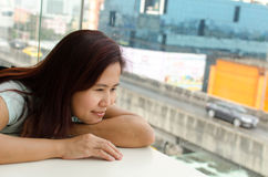 Happy Asian woman. Side profile of Asian woman who is looking outside window Royalty Free Stock Photography