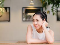 Happy woman is sitting in the cafe with a smile in her face. Happy Asian woman is sitting in the cafe with a smile in her face royalty free stock images
