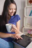 Happy asian woman sitting on the couch holding mug of coffee usi Royalty Free Stock Photos