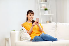 Happy asian woman with smartphone at home Royalty Free Stock Photography