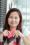 Happy Asian woman. Asian woman is smiling to camera and holding her pink small purse Royalty Free Stock Images