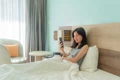 Happy Asian woman smiling, using a mobile phone, chatting with friends on bed in a modern bedroom with white blanket in the. Morning stock photos