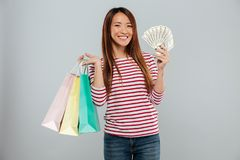Happy asian woman in sweater holding money and packages. While looking at the camera over gray background royalty free stock photos