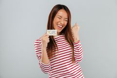 Happy asian woman in sweater rejoice and holding credit card. Over gray background Royalty Free Stock Image