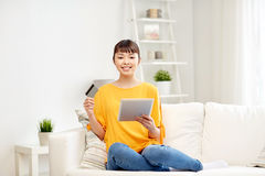 Happy asian woman with tablet pc and credit card Royalty Free Stock Image