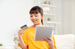 Happy asian woman with tablet pc and credit card Royalty Free Stock Images