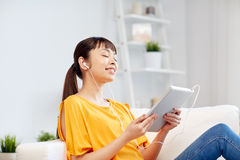 Happy asian woman with tablet pc and earphones Stock Photos