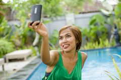 Happy Asian woman taking selfie picture for social media interne Stock Photo