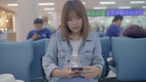 Happy Asian woman using and checking her smartphone in terminal hall while waiting her flight at the departure gate in airport. Happy Asian woman using and stock video