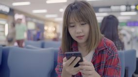 Happy Asian woman using and checking her smartphone in terminal hall while waiting her flight at the departure gate in airport. Happy Asian woman using and stock footage