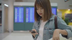 Happy Asian woman using and checking her smartphone in terminal hall while waiting her flight at the departure gate in airport. Happy Asian woman using and stock video footage