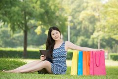 Happy asian woman using digital tablet shopping online with cred Stock Photos