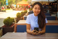Happy asian woman using smart phone while sitting in cafe. royalty free stock image