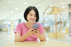 Happy Asian woman using smartphone on table at department store royalty free stock photos