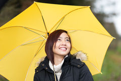 Happy Asian woman walking with an umbrella. Happy attractive young Asian woman walking with a yellow umbrella looking up at the sky with a lovely smile Stock Image