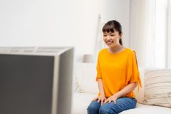 Happy asian woman with watching tv at home. Television, leisure and people concept - happy smiling asian woman watching tv at home Royalty Free Stock Photo