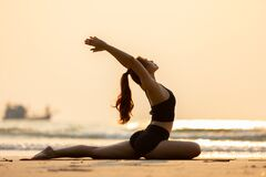 Free Happy Asian Woman Wearing Black Sport Wear Practice Yoga Pigeon Pose On The Beach Royalty Free Stock Images - 173810249