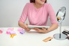Happy asian woman wearing hair curlers using tablet at home royalty free stock photography