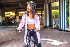 Happy woman wearing helmet riding bicycle in the summer. Happy asian woman wearing helmet riding bicycle in the summer stock photos