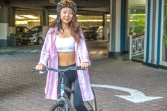 Happy woman wearing helmet riding bicycle in the summer. Happy asian woman wearing helmet riding bicycle in the summer stock image