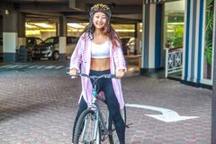 Happy woman wearing helmet riding bicycle in the summer. Happy asian woman wearing helmet riding bicycle in the summer stock photo