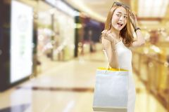 Happy asian woman in white dress with shopping bags at mall royalty free stock images
