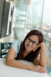 Happy Asian woman. Asian woman who is wearing glasses, sitting in front of glass window, smiling, looking at camera Royalty Free Stock Photos