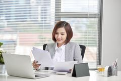 Happy asian woman working in office. Female going through some paperwork at work place.  royalty free stock photos