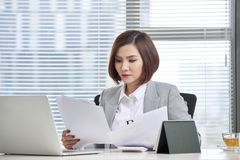 Happy asian woman working in office. Female going through some paperwork at work place.  royalty free stock images
