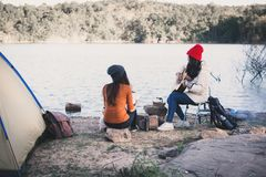 Happy Asian women playing guitar in nature winter season. Relax time on holiday concept travel and camping partnership,selective and soft focus,tone of hipster Royalty Free Stock Image