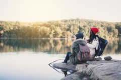 Happy Asian women playing guitar in nature winter season. Relax time on holiday concept travel and camping partnership,selective and soft focus,tone of hipster Stock Photos