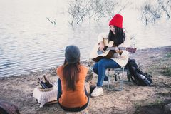 Happy Asian women playing guitar in nature winter season. Relax time on holiday concept travel and camping partnership,selective and soft focus,tone of hipster Stock Images