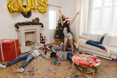 Happy asian woman and drunk friends. Happy asian women in santa claus hat and drunk friends after new year party at home Stock Photo