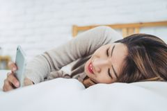 Happy Asian women are using smart phone on the bed in morning. Asian woman in bed checking social apps with smartphone. Happy Asian woman are using smart phone Royalty Free Stock Photos